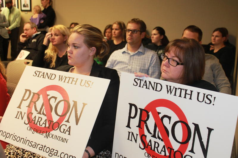 Eagle Mountain residents Shana Clark and Amber Davis holding signs inside the Saratoga Springs City Council meeting.