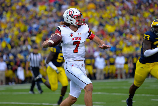 University of Utah football player Travis Wilson rolls out against Michigan in 2014