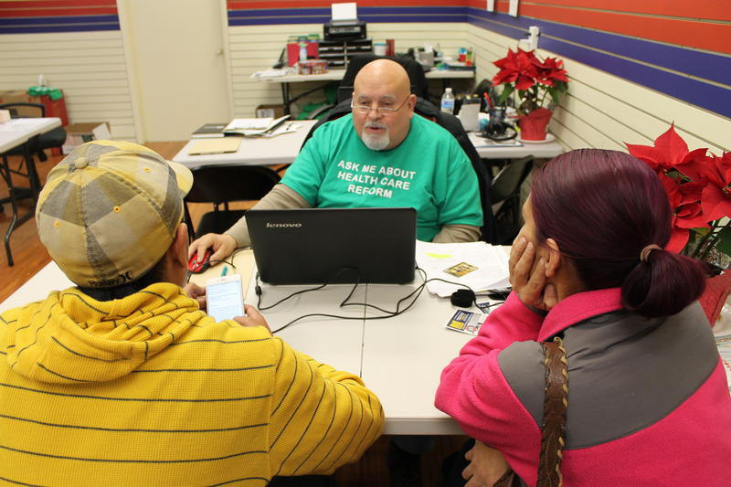 Insurance agent Miguel Palacios helps Armando Pina and Christina Perez buy health insurance for themselves and their five daughters.
