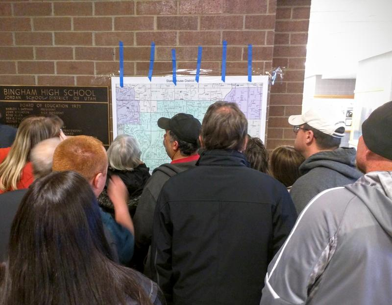 A large group of voters gathers around a precinct map during a Utah GOP Caucus Night