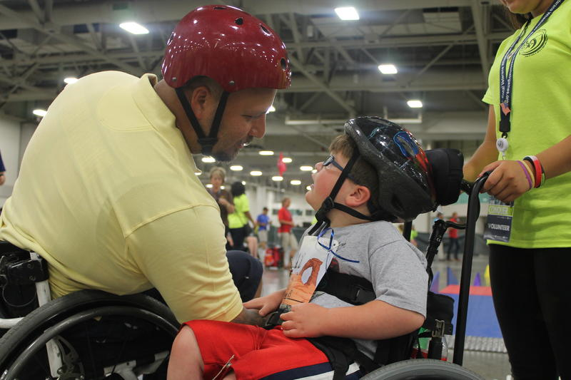 Veteran and mentor Jeff DeLeon talks with a Kids Day participant at the National Veterans Wheelchair Games