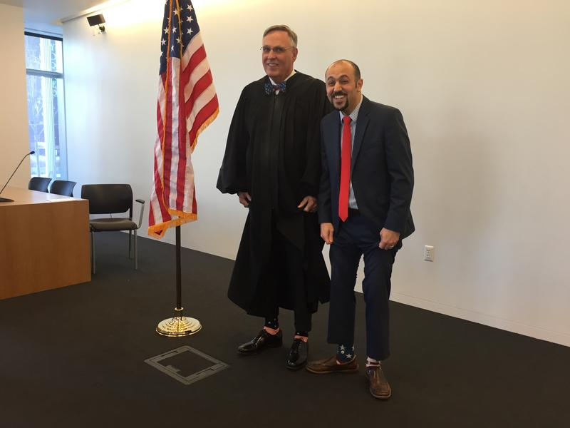Reda Almulhem, from Syria, shows off his patriotic socks next to Judge Paul Warner following a naturalization ceremony at the Salt Lake U.S. District Courthouse on Nov. 9.