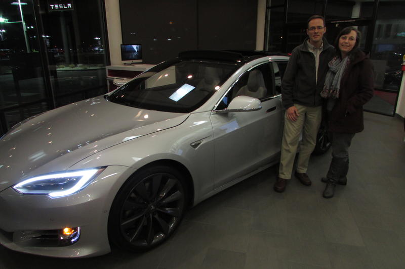 Manny and Loralee Kurzius stand near a similar car to the one they'd just arranged to buy at the Salt Lake City Tesla offices. They love many features, including how it will be fueled by the sun.