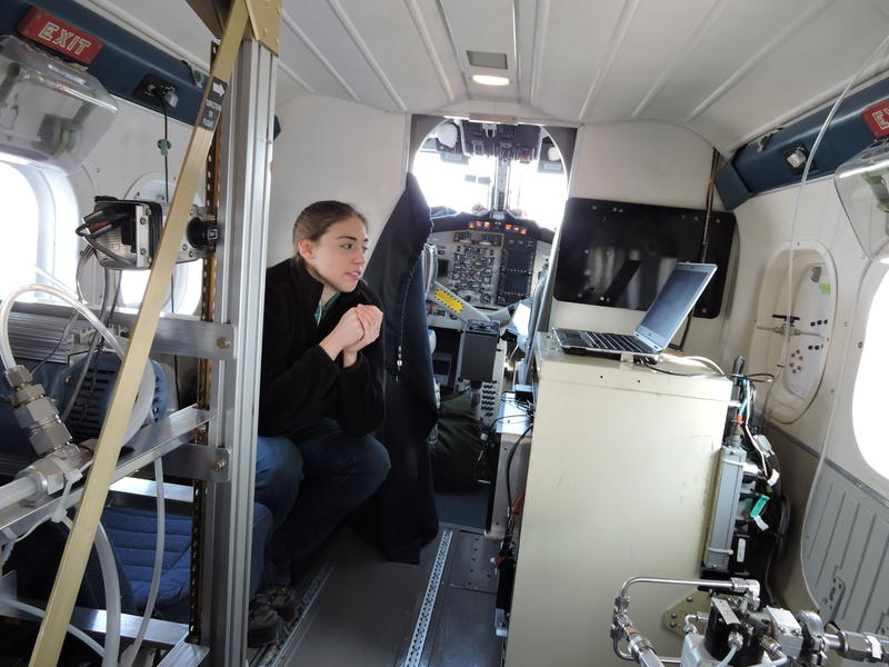 Erin McDuffie of NOAA, on the specially equipped Twin Otter, checks on one of six data-gathering stations in the research aircraft. They're gathering information about the chemicals in the air and how they vary from place to place at different times.