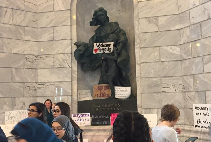 A sign appears in the hands of a statue inside the Utah State Capitol building.