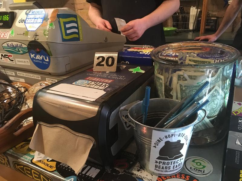 The cash register at Toasters deli is adorned with stickers from the companies and causes represented at the Outdoor Retailers trade show that takes place across the street. The show's moving over a dispute about Utah lands policies.