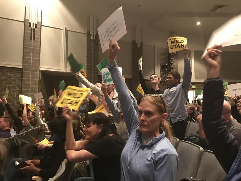 Attendees of Rep. Chris Stewart's town hall hold up signs as he speaks. About 1,100 packed the auditorium at West High School on March 31 for Stewart's first in-person forum since his re-election.