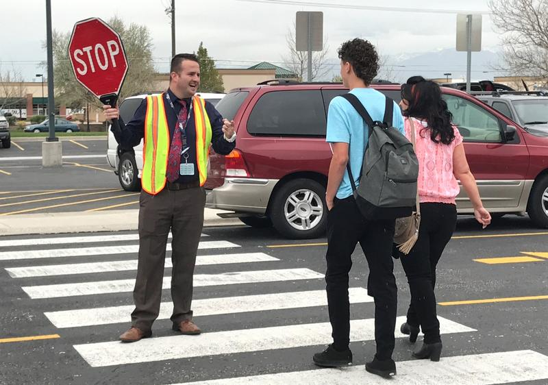 Spencer Campbell, Assistant Principal of Elk Ridge Middle School, helps students cross the street at the end of a school day.