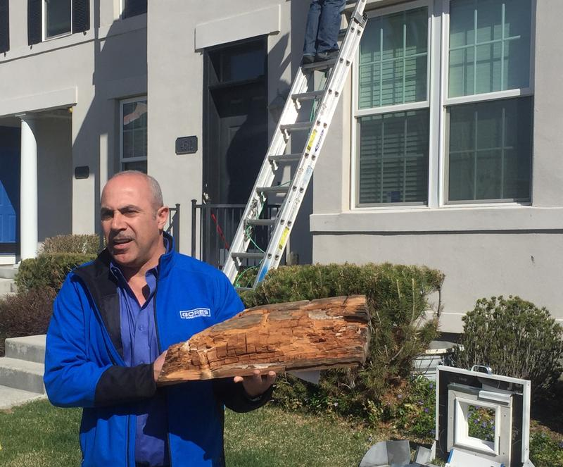 Sean Gores shows off water-damaged wood from a unit in Daybreak.