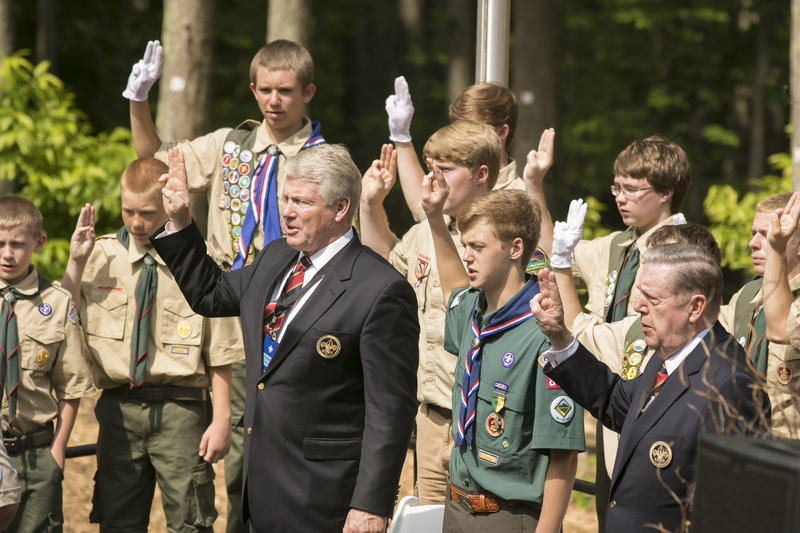 Elder Jeffrey R. Holland, on the right, and Stephen W. Owen, Young Men general president in The Church of Jesus Christ of Latter-day Saints in the middle, show the Scout sign with a group of Boy Scouts and recite the Scout Oath.