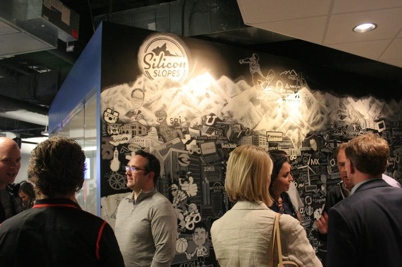 Visitors stand in front of a mural at the new headquarters of Silicon Slopes in Lehi.