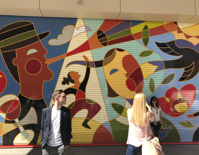 People pose in front of a mural on the back of the Eccles Theater in Salt Lake City.