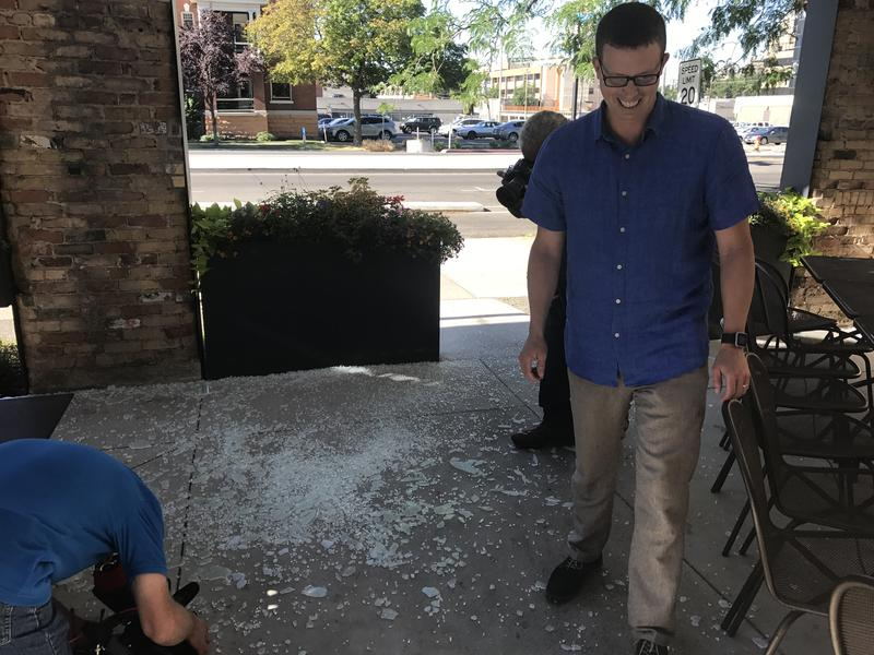 Current general manager Andrew Cliburn smiles after he throws and breaks what used to be part of the seafood restaurant's state-mandated Zion Curtain barrier.