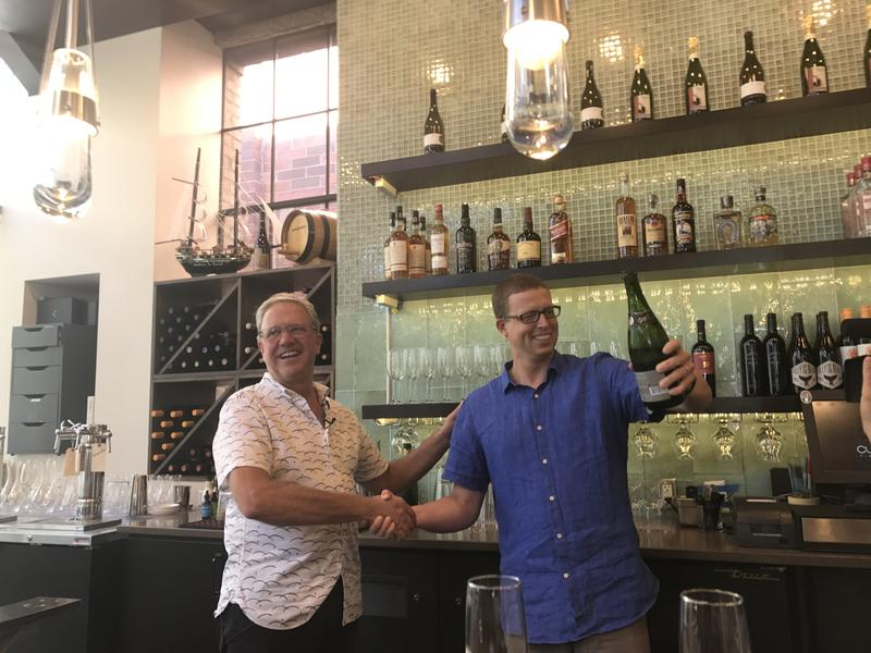 Current Fish & Oyster owner Joel LaSalle (left) and general manager Andrew Cliburn celebrate removal of their bar's barrier with a champagne toast.