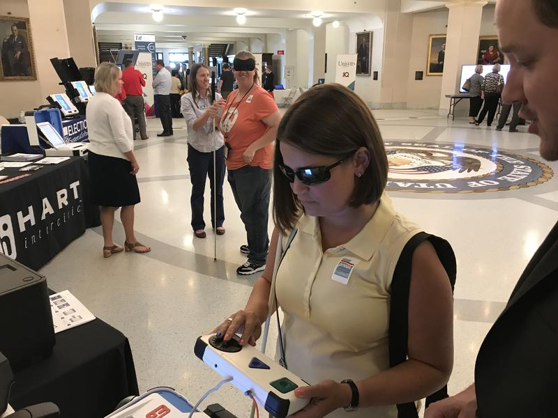 Jennifer Kennedy tests out a voting machine with audio ballot from Austin, Texas-based Hart Intercivic. Kennedy advocates for making voting easier for those with visual impairments.