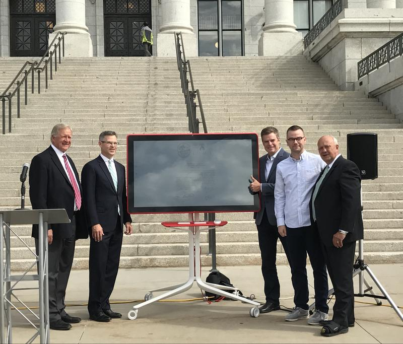Tech and business leaders stand beside a new partnership agreement, which was signed on an electronic board.