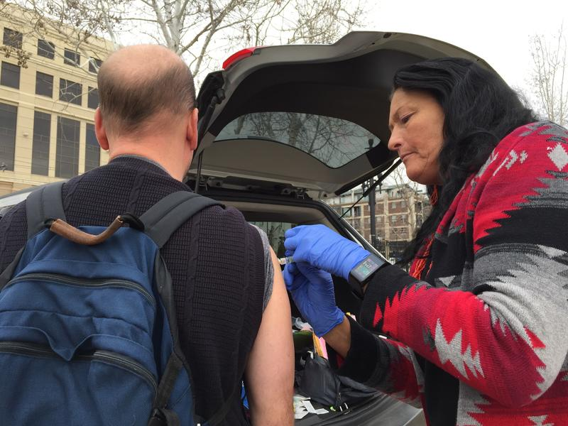 Salt Lake County employee Terry Begay gives hepatits A vaccine outside the Weigand Homeless Resource Center.