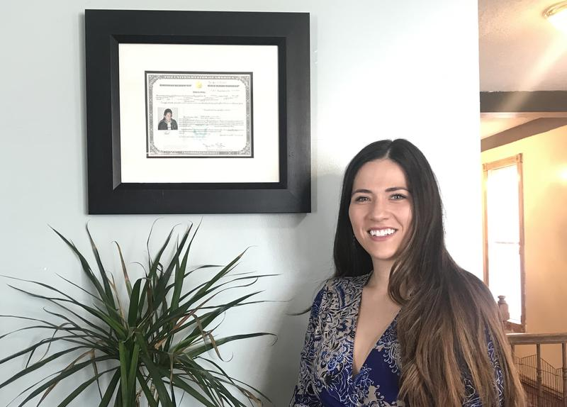 Isabel Cueva stands in front of her naturalization certificate in her Salt Lake City home.
