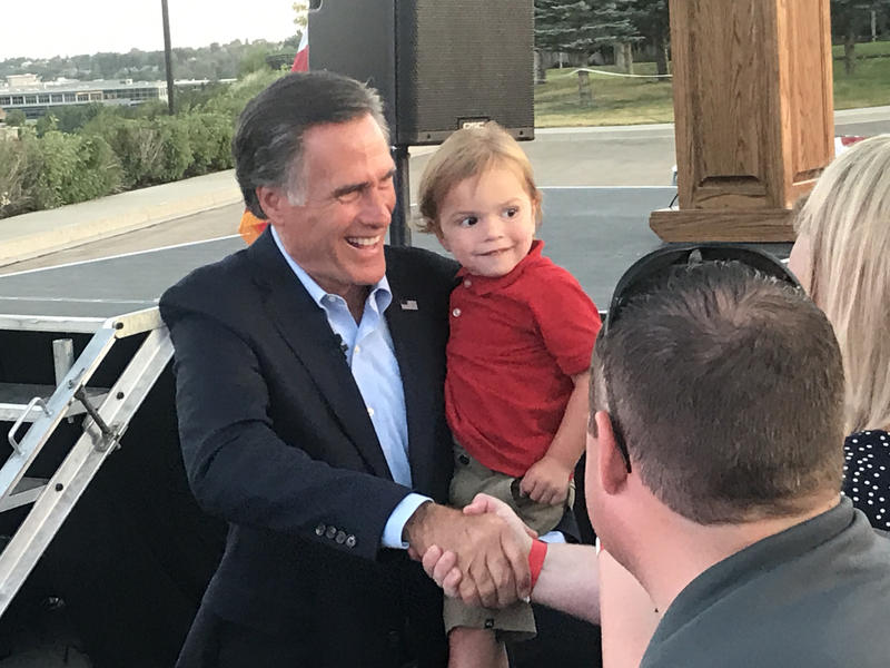 Mitt Romney shaking hands and holding his two-year-old grandson, Dane.