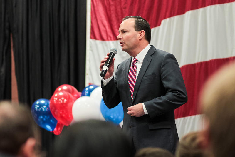 Senator Mike Lee speaks into a microphone in front of american flag and balloons.