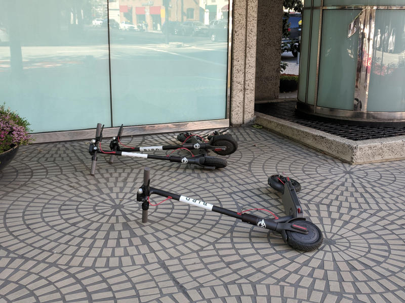 Three razr scooter style electric scooters lay on their side on the sidewalk.