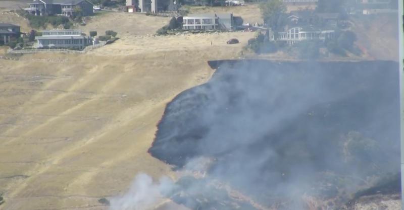 Burn scars on brown grass behind Utah Capitol.