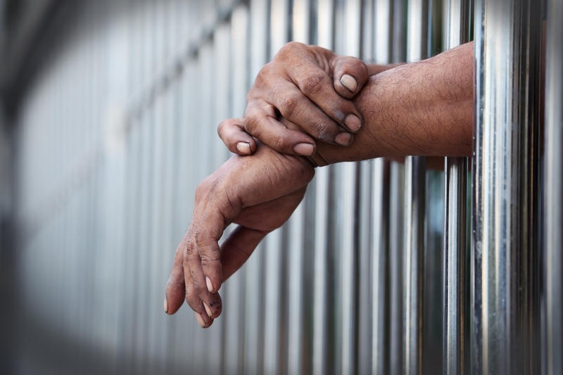 The hands of an unidentified inmate rest outside the bars of a holding cell.
