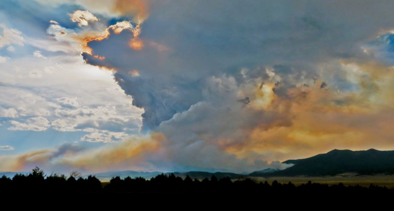 Smoke plumes from wildfires in front of clouds.