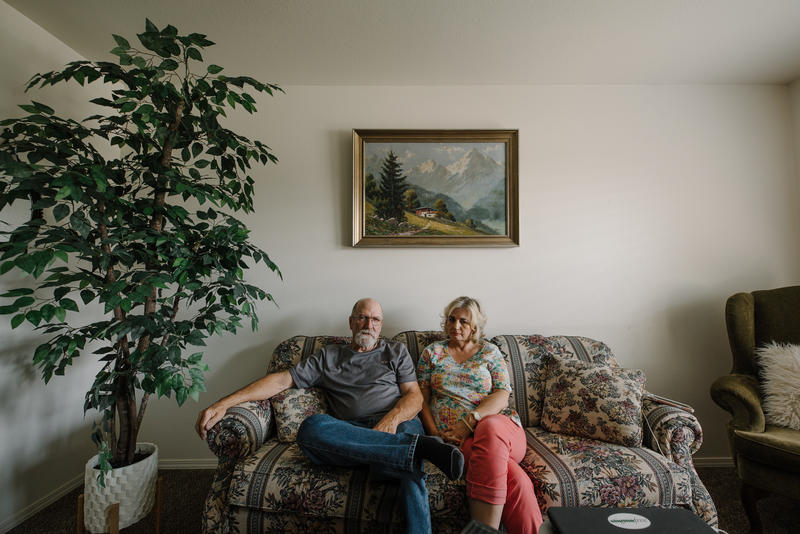 Sherry and Marc Hunter sit on their couch.