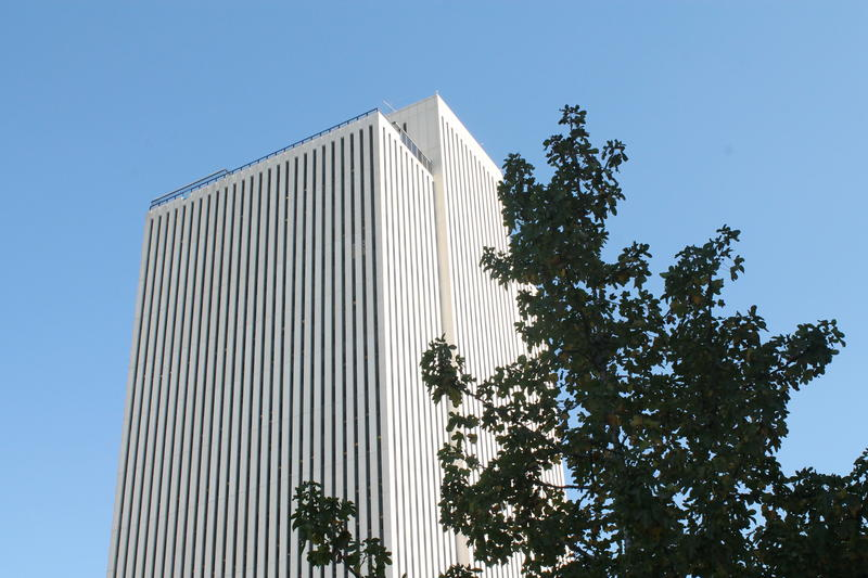 A tall white building against blue sky.
