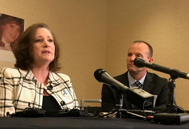 Denson speaks at a podium alongside her lawyer.