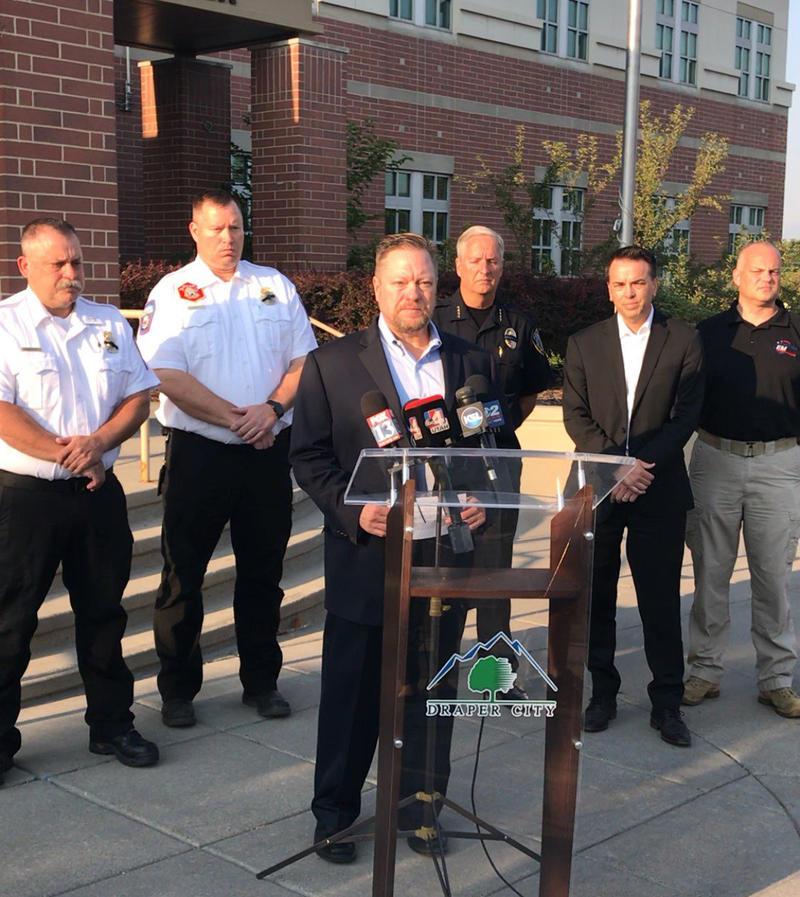 Draper Mayor Troy Walker speaks at podium in front of 5 firefighters.