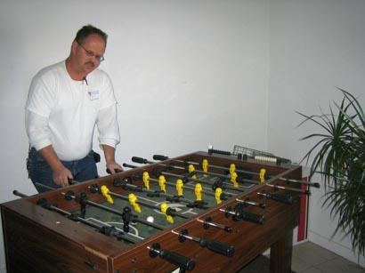 Ray Dumas playing foosball in his apartment