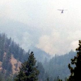 Helicopters are gathering water from the nearby Clark Fork river to drop on the West Mullan fire