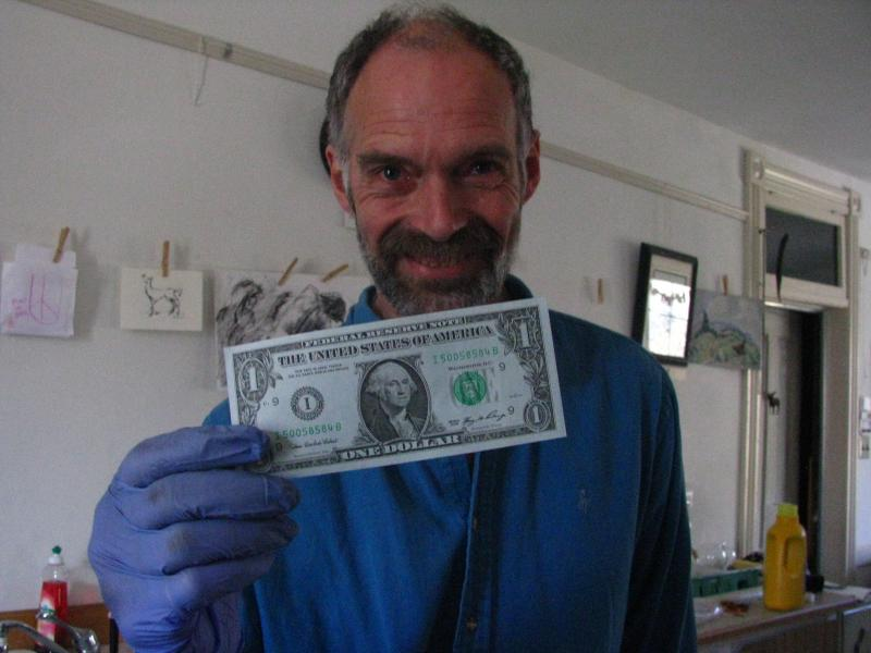 Tim Holmes holds up one of his blue dollar bills Thursday.