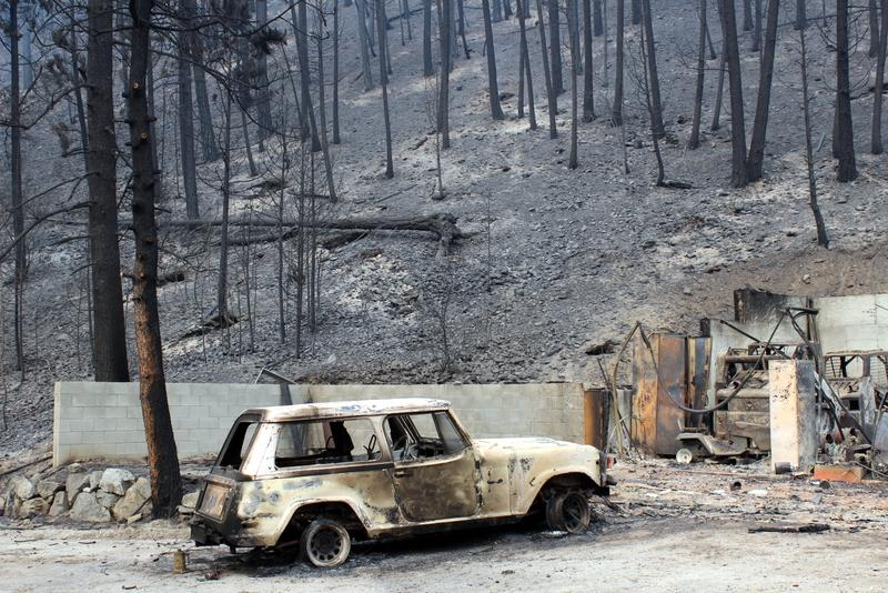 Burned out vehicle and scorched hillside