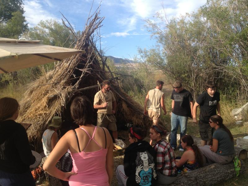 PAL's 'Primitive Elements' Class gathers around one of the group's shelters to practice starting a fire with a 'bow-drill'