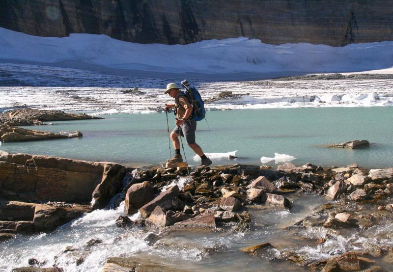 Dan Fagre crosses a rocky path next to a waterfall on his way to Grinnell Glacier.