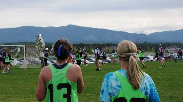 Girls from the Missoula team watch as their teammates play Helena during the state lacrosse championship tournament.