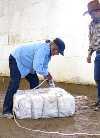 A  workshop participant practices wrapping and tying up a gear box for a horse to pack.