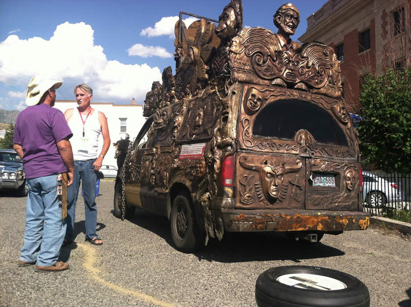 "Scott Campbell, AKA ""Extremo the Clown, AKA Portland Monkey Man talks with a Montana Folk Festival visitor next to his 2003 Chevy Astro which he converted into a bronze-colored work of art on wheels."
