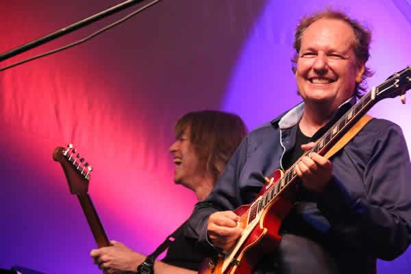 Mike Stern and Lee Ritenour having fun on stage.
