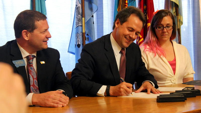 Gov. Bullock signs the Medicaid expansion plan into law, April 29, 2015 at the state Capitol. The bill's sponsor Sen. Ed Buttrey, and supporter Stephanie Wallace look on.