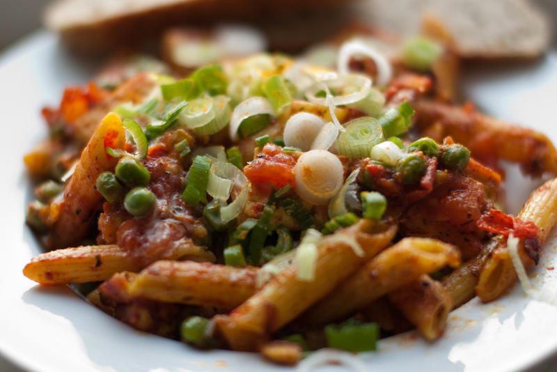Penne pasta in spicy tomato sauce with peas and green onions. (CC BY-NC-2.0)