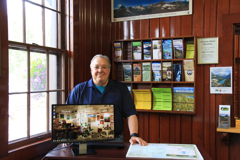 Visitor center attendant Hugh Austin stands behind the information desk at the old Belton Train Station in West Glacier. The visitor center is staffed 1-5pm, 7 days a week, and will provide Glacier visitors information on activities around the Flathead.