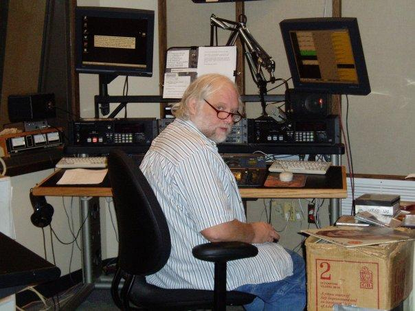 A 2005 photo of John Myers in Master Control, flying the mothership. His trademark duct-taped cardboard box-of-show is next to him, full of vinyl records, lined up in broadcast order for the evening's program.