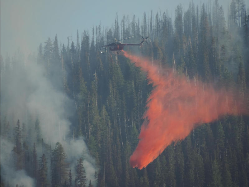 Sikorsky Sky Crane Type-1 Helicopter drops fire retardant on the Thompson-Divide Complex's Sheep Fire burning west of Highway 2 between Mile Markers 182 and 181 about 1 mile south of Essex, MT, Aug. 22, 2015.