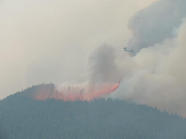 The Billings Chinook Type-1 Helicopter drops fire retardant from the mobile retardant base onto the Sheep Fire, part of the Thompson-Divide Complex, burning near Highway 2 about 2 miles south of Essex, MT, Aug. 20, 2015.