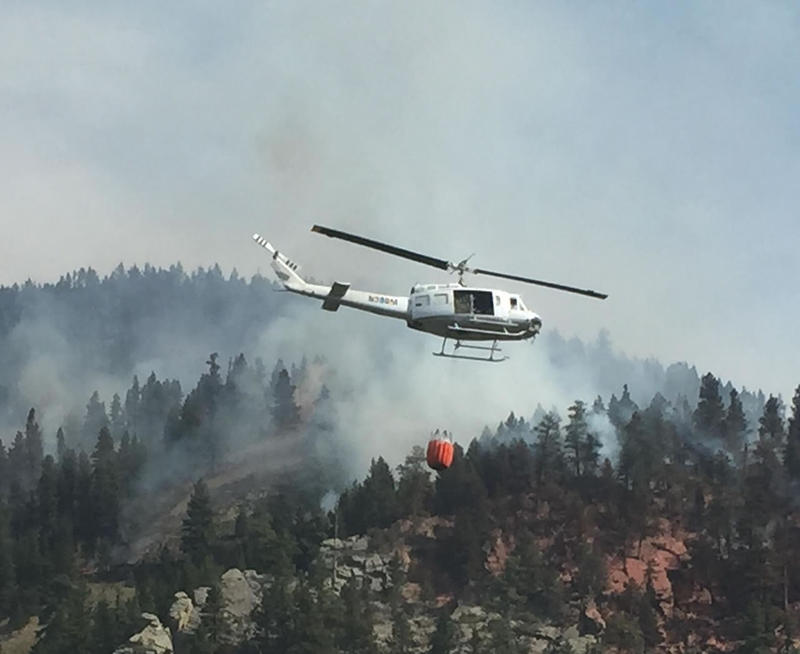 A helicopter drops water on a fire in the Holter Complex.