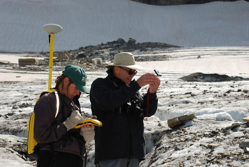 Scientists measuring the terminus of Grinnell Glacier, in Glacier National Park.
